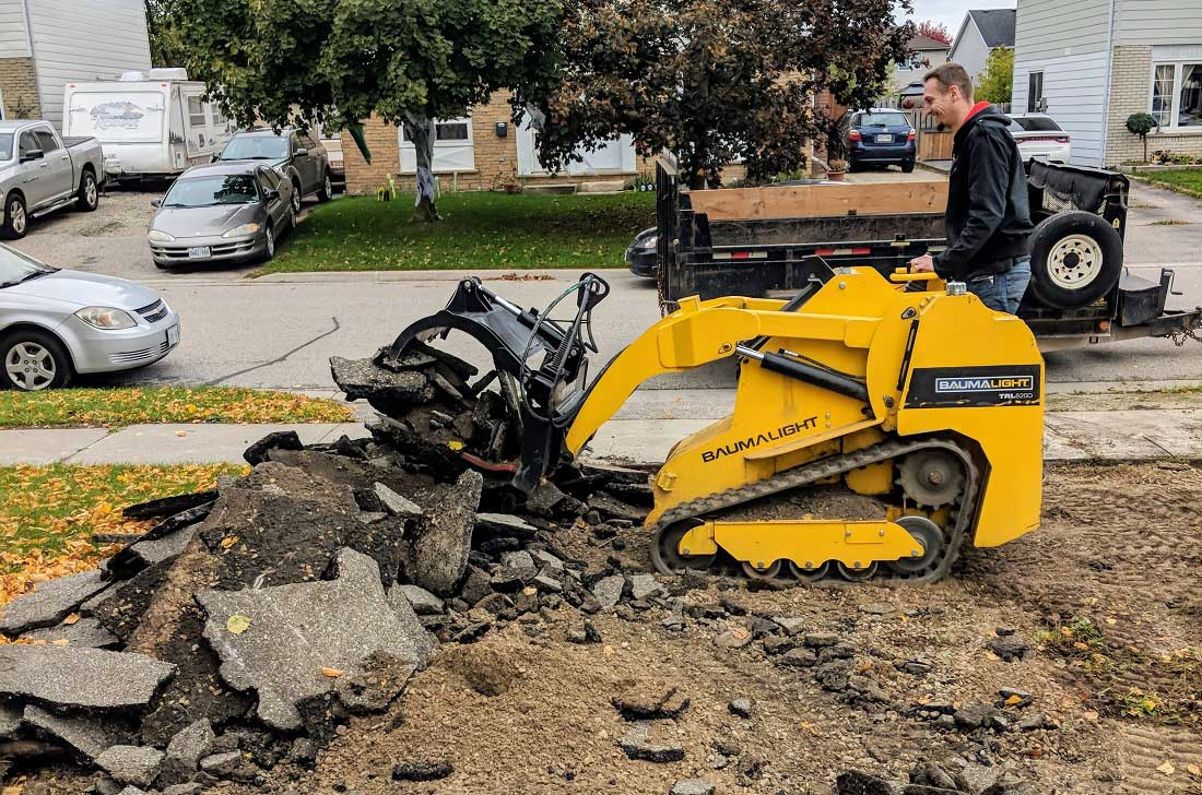 Mini skidsteer in rough work with grabble