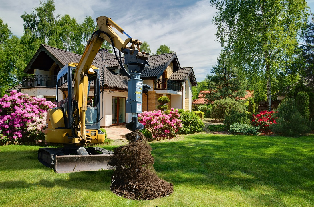 Planting tress with excavator mounted Auger